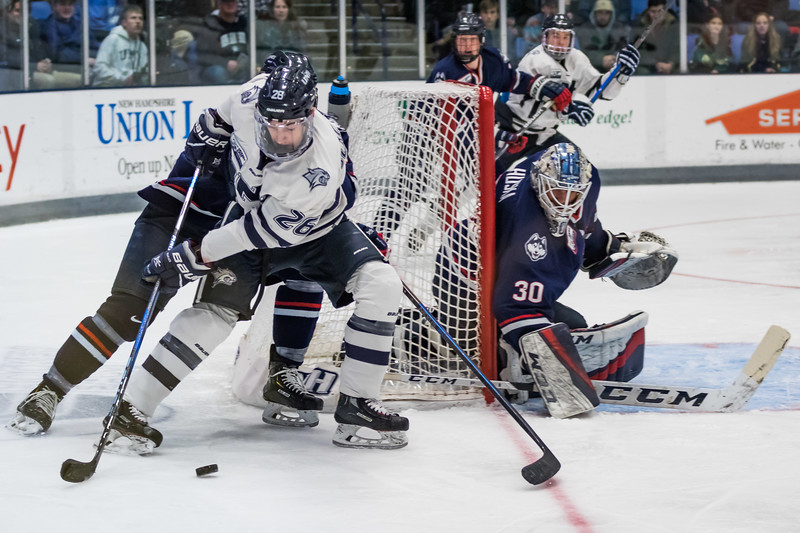 New Hampshire's Liam Blackburn (26) looks to pass the puck while being defended by Connecticut's Roman Kinal during Hockey East action in Durham Saturday. [Scott Patterson/Fosters.com]