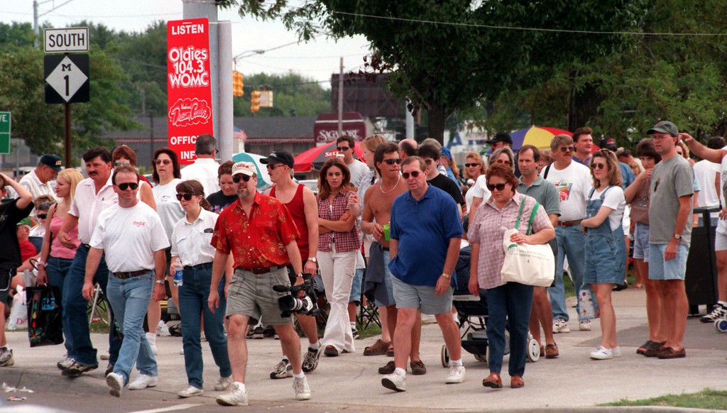. Spectators make their way across 13 mile road in Royal Oak near Woodward Ave. during the Fifth Annual Woodward Dream Cruise.
