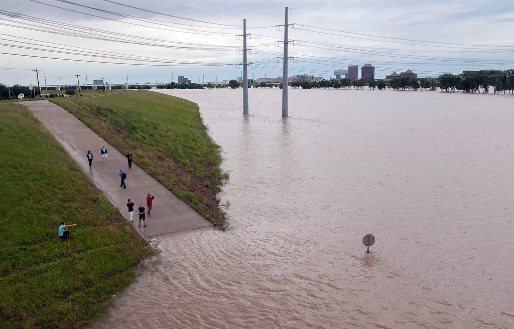 . Curious onlookers walk along a closed path next to the Trinity River in Dallas on Saturday, May 30, 2015.  The National Weather Service has issued a flood watch for portions of Central and South Texas, which could see as much as five inches of rain Saturday if a storm system stalls over the area. (AP Photo/Rex C. Curry)