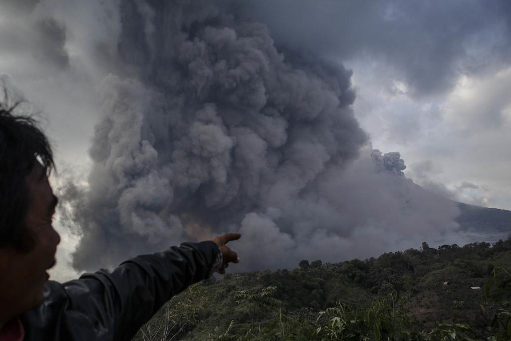 . A man watches as Mount Sinabung spews pyroclastic smoke at Tiga Pancur village on October 13, 2014 in Berastagi, Karo district, North Sumatra, Indonesia.  (Photo by Ulet Ifansasti/Getty Images)