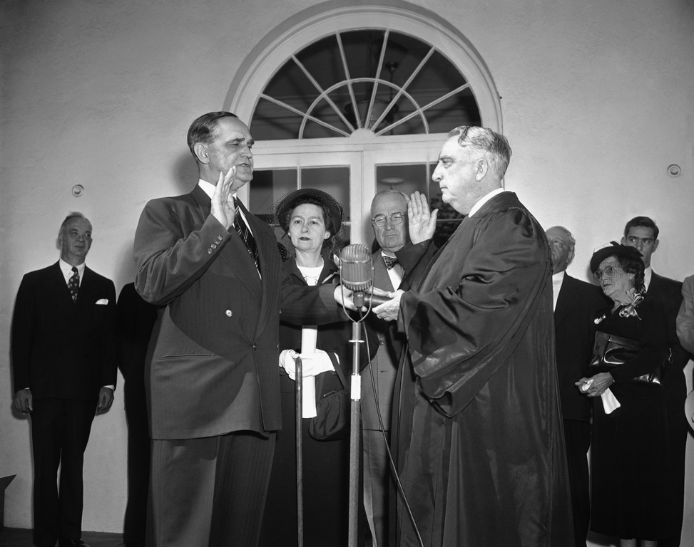 . Sherman Minton, left, former Indiana Senator, repeats the oath of office as U.S. Supreme Court Justice during a ceremony with Chief Justice Fred Vinson, right, officiating on the White House steps, Oct. 12, 1949, Washington, D.C. Mrs. Minton and Pres. Harry S. Truman are at center. (AP Photo/John Rous)