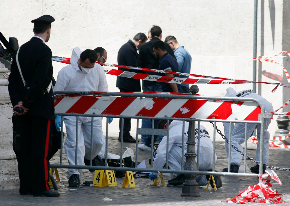 . Carabinieri forensic investigators survey around the area where gunshots were fired, in front of Chigi Palace, in Rome April 28, 2013. Two police officers were shot and wounded outside the Italian prime minister\'s office on Sunday as Enrico Letta\'s new government was being sworn in around a km (0.62 miles) away at the president\'s palace, RAI state television reported. REUTERS/Remo Casilli
