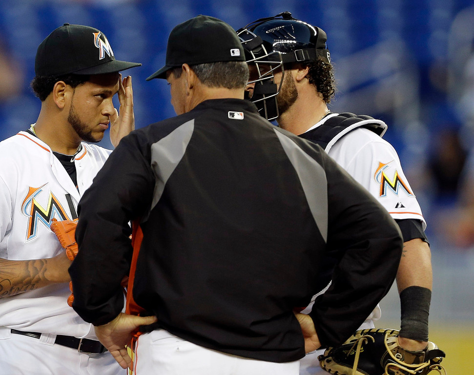 . Miami Marlins\' Henderson Alvarez, left, talks with pitching coach Chuck Hernandez, center, and catcher Jarrod Saltalamacchia, right, in the first inning of a baseball game against the Colorado Rockies, Wednesday, April 2, 2014, in Miami. (AP Photo/Lynne Sladky)