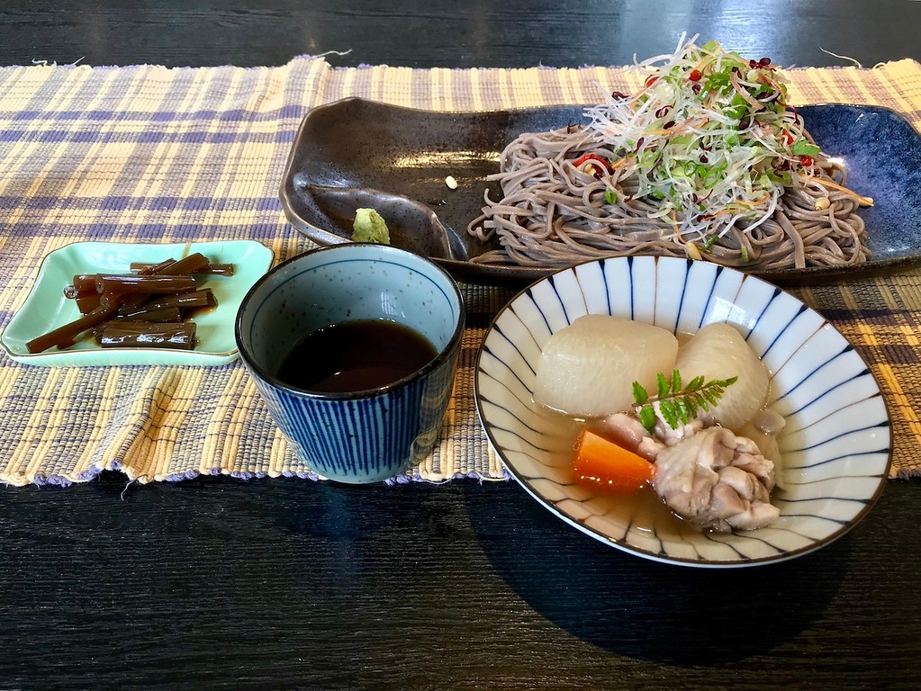 Soba buckwheat noodles with vegetables, simmered chicken and root vegetables, braised butterbur stalks, and a noodle dipping sauce.