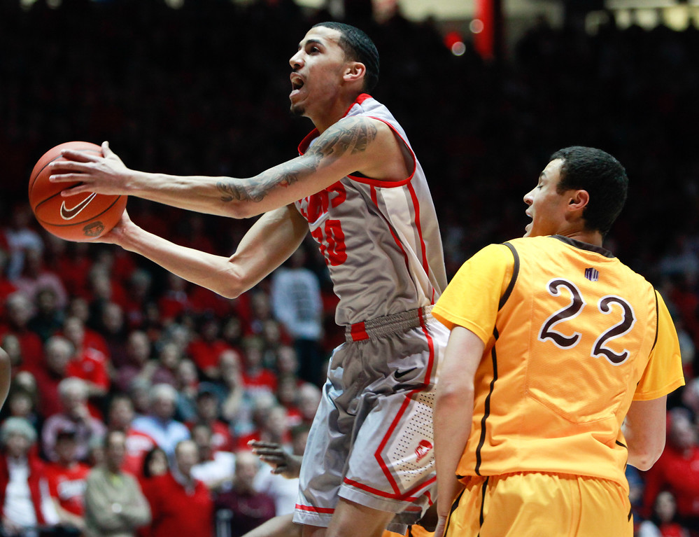 . New Mexico\'s Kendal Williams tries for a layup as he goes past Wyoming\'s Larry Gilmore Jr. during the first half of an NCAA college basketball game in Albuquerque, N.M., Saturday, March 2, 2013. (AP Photo/Craig Fritz)