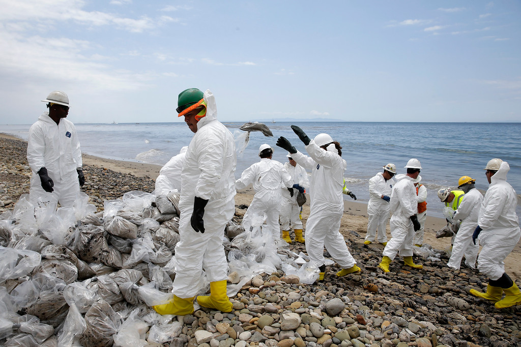 . Clean up workers gather oil-contaminated sand bags at Refugio State Beach, north of Goleta, Calif., Thursday, May 21, 2015. More than 7,700 gallons of oil has been raked, skimmed and vacuumed from a spill that stretched across 9 miles of California coast, just a fraction of the oil escaped from a broken pipeline, officials said. (AP Photo/Jae C. Hong)