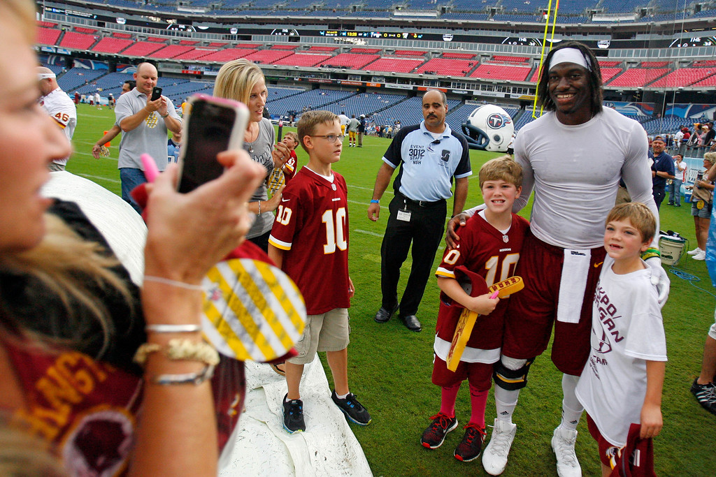 . Washington Redskins quarterback Robert Griffin III poses for photos with fans before a preseason NFL football game against the Tennessee Titans, Thursday, Aug. 8, 2013, in Nashville, Tenn. (AP Photo/Mark Zaleski)