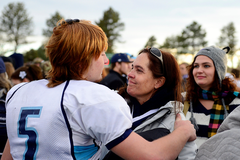. Marilyn Johnson hugs quarterback Logan Stitzman following Platte Valley\'s 28-17 state title loss to Kent Denver. Though Trey could not attend, Marilyn attended in support of the team. AAron Ontiveroz, The Denver Post