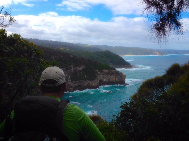 A boomer man looks out at the blue ocean from Ryan's Den on the Great Ocean Road.