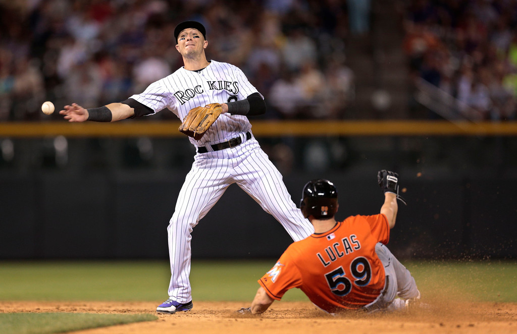 . Colorado Rockies shortstop Troy Tulowitzki, left, forces out Florida Marlins\' Ed Lucas (59) at second base on an attempted double play in the eighth inning of a baseball game in Denver, Wednesday, July 24, 2013. Tulowitzki overthrew first base. Marlins\' Placido Polanco advanced to second on the error and later scored. (AP Photo/Joe Mahoney)
