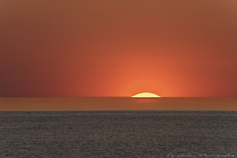 June 3rd, 2008 - I drove at the lake for the sunset and I was stunned. It is rarely that clear, you could see the ball of fire disappearing without seconds. I shot this one at 300mm. Have a great day ! JY