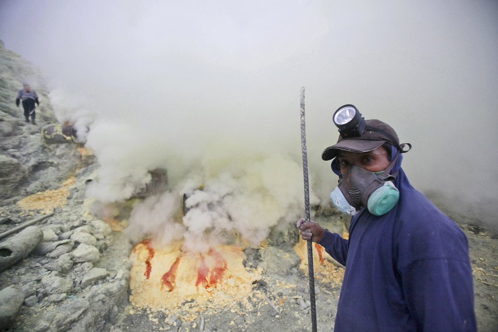 . In this April 16, 2016 photo, a sulfur miner pauses as he works at the crater of Mount Ijen in Banyuwangi, East Java, Indonesia.  (AP Photo/Binsar Bakkara)