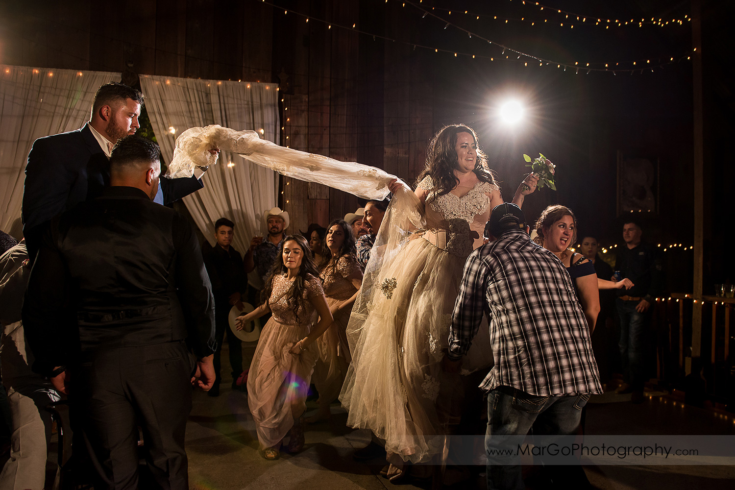 bride and groom standing on chairs during La Vibora de La Mar - the Sea Snake dance with female part of wedding guests at Taber Ranch Vineyards
