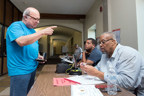 08/14/18 Wesley Bunnell | Staff William Eltman registers to vote at voting district 5-1 at the School Apartments on Bassett St on Tuesday afternoon with the help of Official Checker Harry Hardy as Assistant Registrar Christian Hardy looks on.