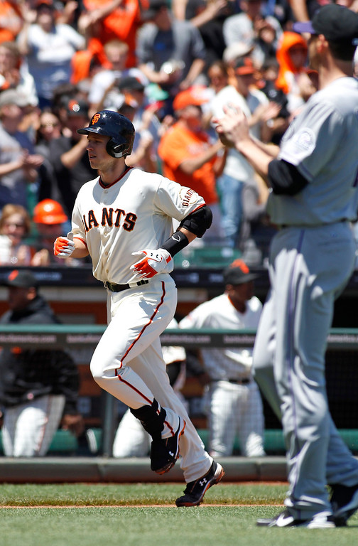 . Colorado Rockies pitcher Jon Garland, right, watches as San Francisco Giants\' Buster Posey runs toward home plate after hitting a home run during the second inning of a baseball game on Sunday, May 26, 2013, in San Francisco. (AP Photo/George Nikitin)