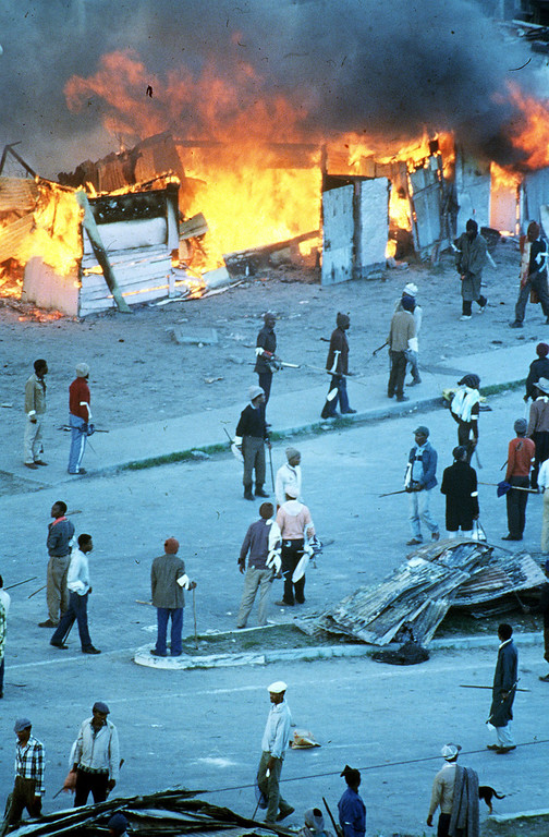 ". Crossroads burning - Vast sections of the Crossroads squatter settlement near Cape Town, home to more than 100,000 people, lay in ruins on May 21, 1986, after four days of raging battles between rival black conservative vigilants and anti-apartheid militants. The death toll is said to have risen to 26 and as many as 50,000 were reported homeless. The U.S. ambassador to South Africa, Herman Nickel called it "" a human disaster of major proportions\"". (AP-Photo/Argus) 21.5.1986"