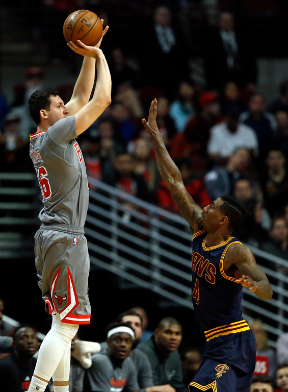 . Chicago Bulls forward Paul Zipser, left, shoots against Cleveland Cavaliers guard Iman Shumpert during the first half of an NBA basketball game Thursday, March 30, 2017, in Chicago. (AP Photo/Nam Y. Huh)