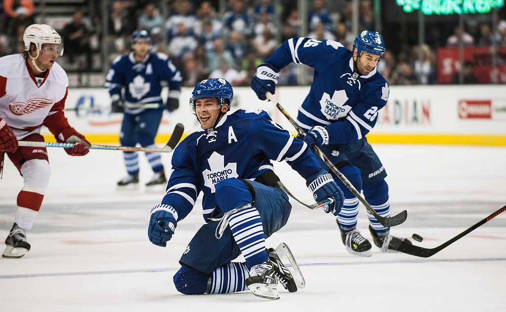 . Toronto Maple Leafs\' Joffrey Lupul, center, recovers from a check against the Detroit Red Wings during second-period preseason NHL hockey game action in Toronto, Friday, Oct. 3, 2014. (AP Photo/The Canadian Press, Aaron Vincent Elkaim)
