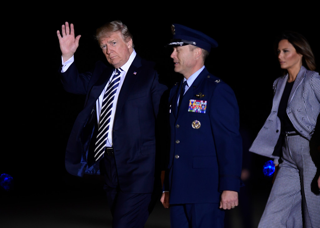 . President Donald Trump, with first lady Melania Trump, far right, waves his hand as they arrive at Andrews Air Force Base in Md., to greet the three Americans detained in North Korea for more than a year, Thursday, May 10, 2018. (AP Photo/Susan Walsh)