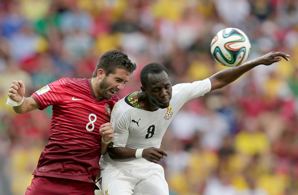 . Ghana\'s Afriyie Acquah and Portugal\'s Joao Moutinho, left, go for a header during the group G World Cup soccer match between Portugal and Ghana at the Estadio Nacional in Brasilia, Brazil, Thursday, June 26, 2014. (AP Photo/Marcio Jose Sanchez)