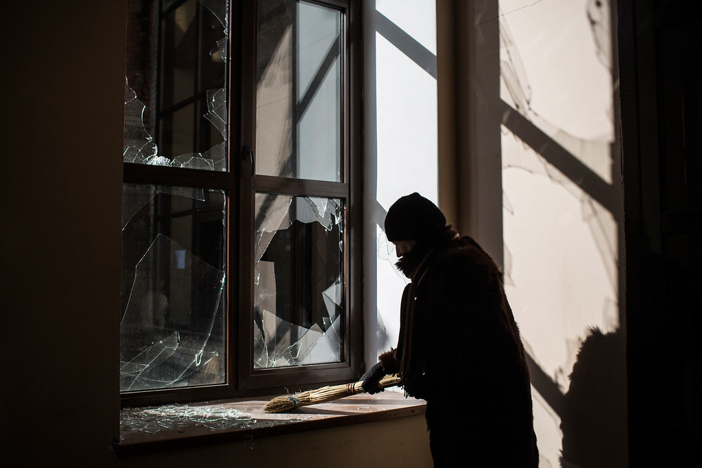 . DEBALTSEVE, UKRAINE - FEBRUARY 25:  A woman cleans up broken glass at the partially destroyed Debaltseve train station on February 25, 2015 in Debaltseve, Ukraine. After approximately one month of fighting, Russian backed rebels successfully forced Ukrainian troops to withdraw from the town of 100,00 people on February 18. Only approximately 11,000 civilians remain in the town. Debaltseve is considered an asset to both Ukrainians and the rebels due to the railway station and it\'s connection to other eastern Ukranian towns.  (Photo by Andrew Burton/Getty Images)