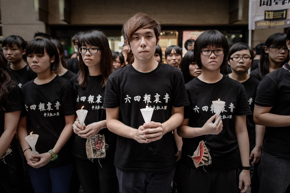 . Students hold candles before performing a song in a street leading to a candlelight vigil held to mark the 24th anniversary of the 1989 crackdown at Tiananmen Square, in Hong Kong on June 4, 2013.  More than 100,000 people were expected to attend the candlelight vigil in the former British colony which is the only place in China where the brutal military intervention that ended weeks of nationwide democracy protests in 1989 is openly commemorated.  PHILIPPE LOPEZ/AFP/Getty Images