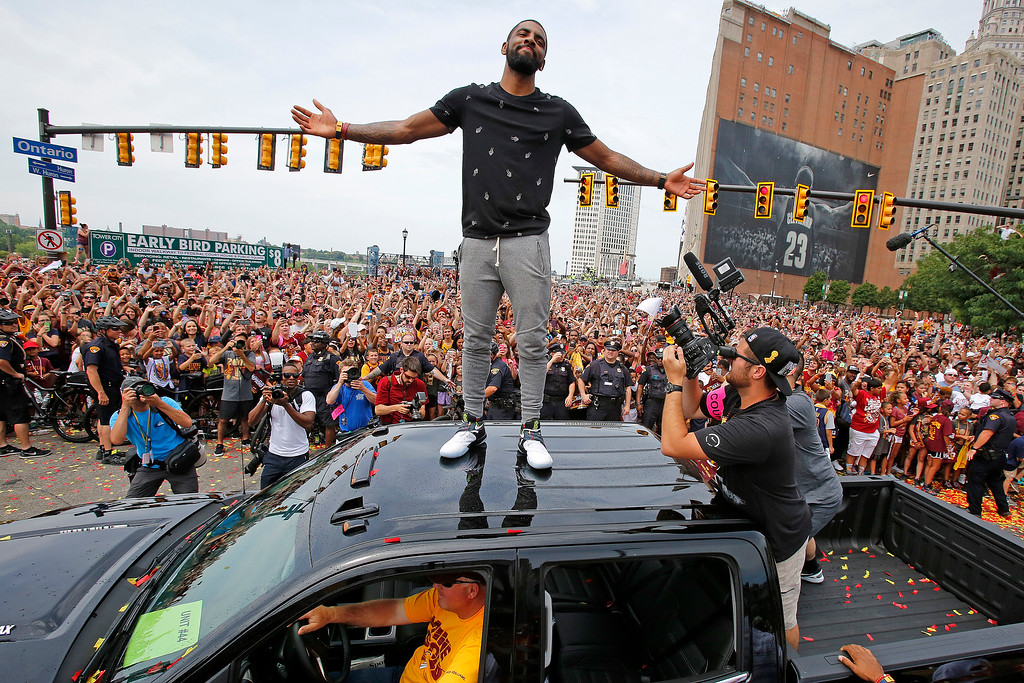 . FILE - In this June 22, 2016, file photo, Cleveland Cavaliers\' Kyrie Irving stands on the roof of a pickup truck before a parade celebrating the NBA basketball team\'s championship, in downtown Cleveland. Four months after LeBron James and the Cavaliers ended the city�s championship drought at 52 years by winning the NBA title, the Indians are back in the World Series for the first time since 1997.  ( (AP Photo/Gene J. Puskar, File)