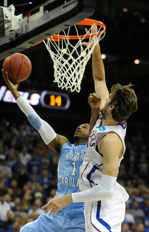 . North Carolina Tar Heels guard Dexter Strickland (L) goes for a shot against Kansas Jayhawks center Jeff Withey during the first half of the third round of the NCAA men\'s basketball tournament at the Sprint Center in Kansas City, Missouri March 24, 2013. REUTERS/Dave Kaup