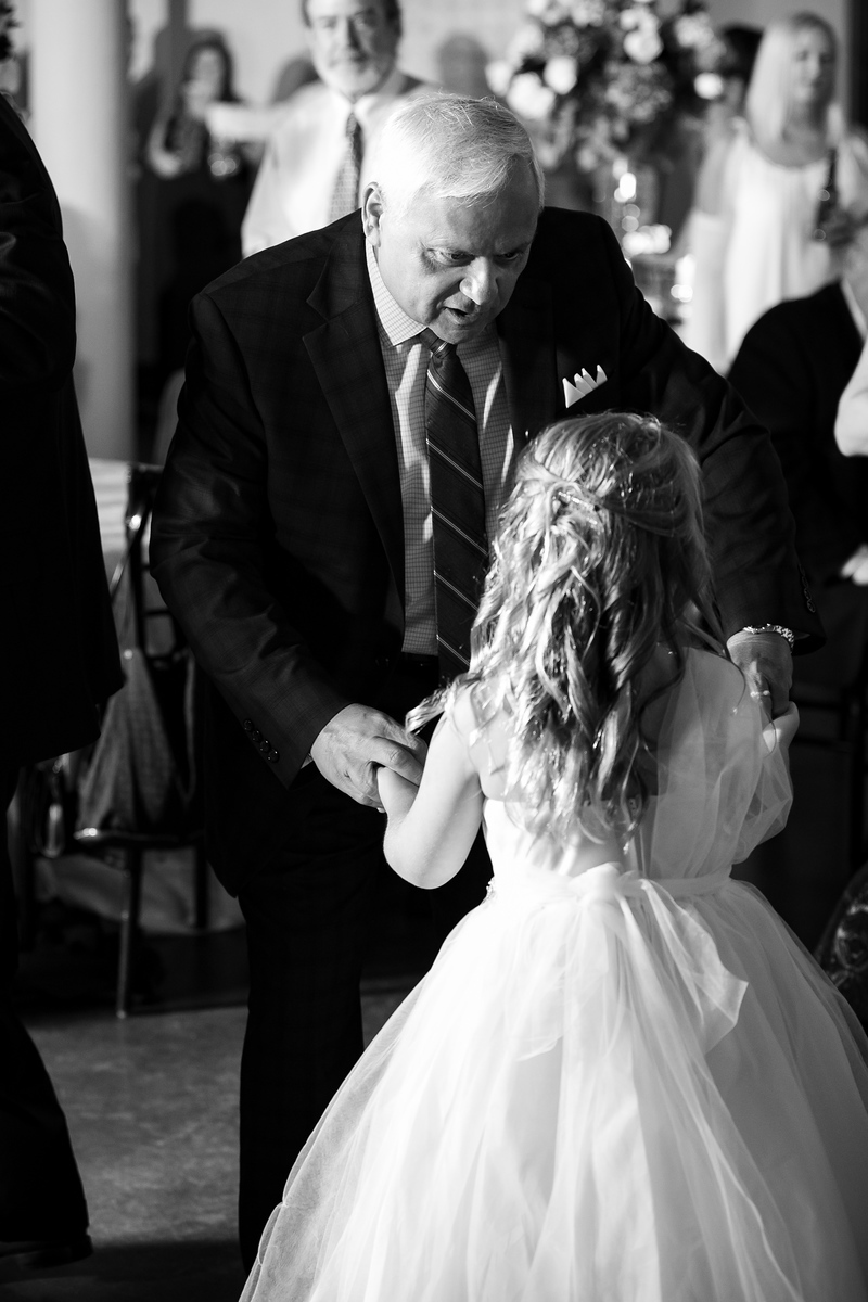 an older man dancing with the flower girl at a wedding