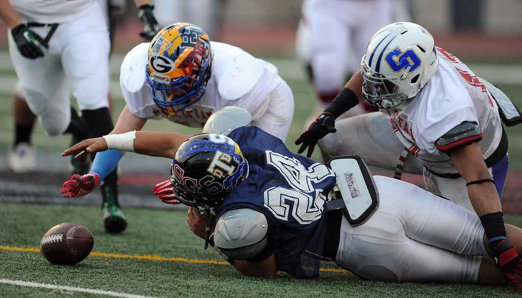 . West\'s Roger Lemus (24) (Lincoln)  reaches for a loose ball in the first half of the annual East vs. West San Gabriel Valley Hall of Fame all-star football game at West Covina High School on Friday, May 17, 2013 in West Covina, Calif. 