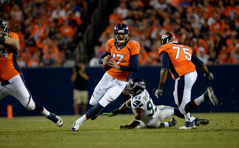 . Quarterback Brock Osweiler (17) of the Denver Broncos avoids a tackle by defensive end O\'Brien Schofield (93) of the Seattle Seahawks during the first half.  The Denver Broncos vs the Seattle Seahawks At Sports Authority Field at Mile High. (Photo by AAron Ontiveroz/The Denver Post)