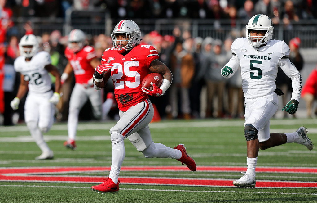 . Ohio State running back Mike Weber, left, outruns the Michigan State defense to score a touchdown during the first half of an NCAA college football game Saturday, Nov. 11, 2017, in Columbus, Ohio. (AP Photo/Jay LaPrete)