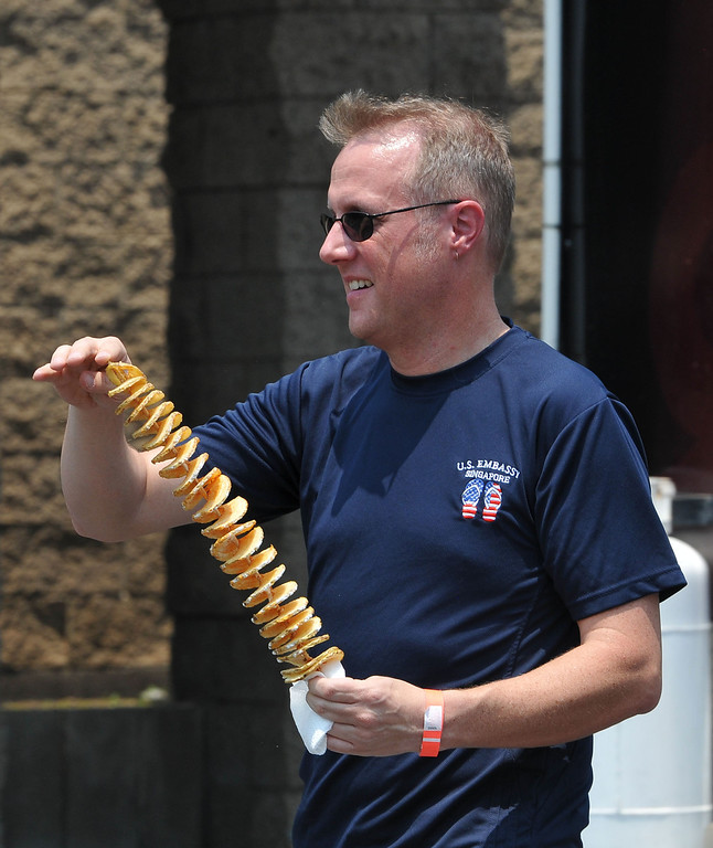 . (John Valenzuela/Staff Photographer) Beau Yarbrough of Redlands walks with his order of spiral potatoes from the during the second annual Food Truck and Brewfest in Redlands Saturday, June 29, 2013.