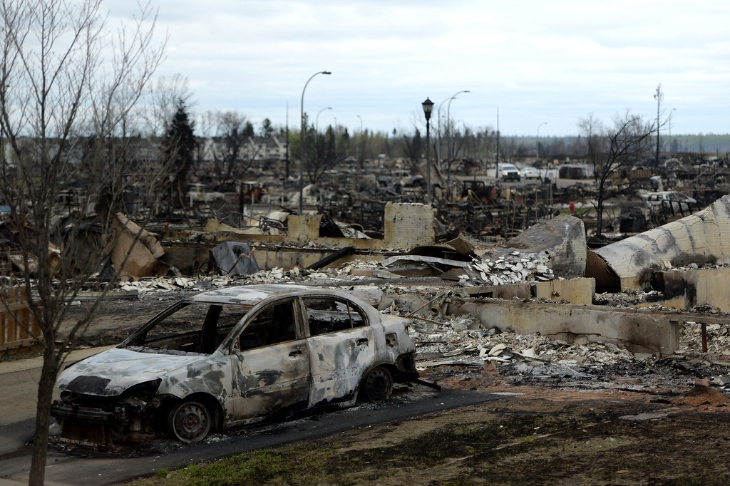 . A burned out car and houses are viewed in the Beacon Hill neighborhood during a media tour of the fire-damaged city of Fort McMurray, Alberta, Monday, May 9, 2016. A break in the weather has officials optimistic they have reached a turning point on getting a handle on the massive wildfire. (Jonathan Hayward/The Canadian Press via AP)