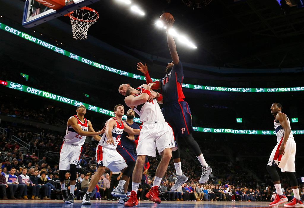 . Detroit Pistons forward Greg Monroe (10) shoots on Washington Wizards center Marcin Gortat (4) in the first half of an NBA basketball game in Auburn Hills, Mich., Sunday, Feb. 22, 2015. (AP Photo/Paul Sancya)