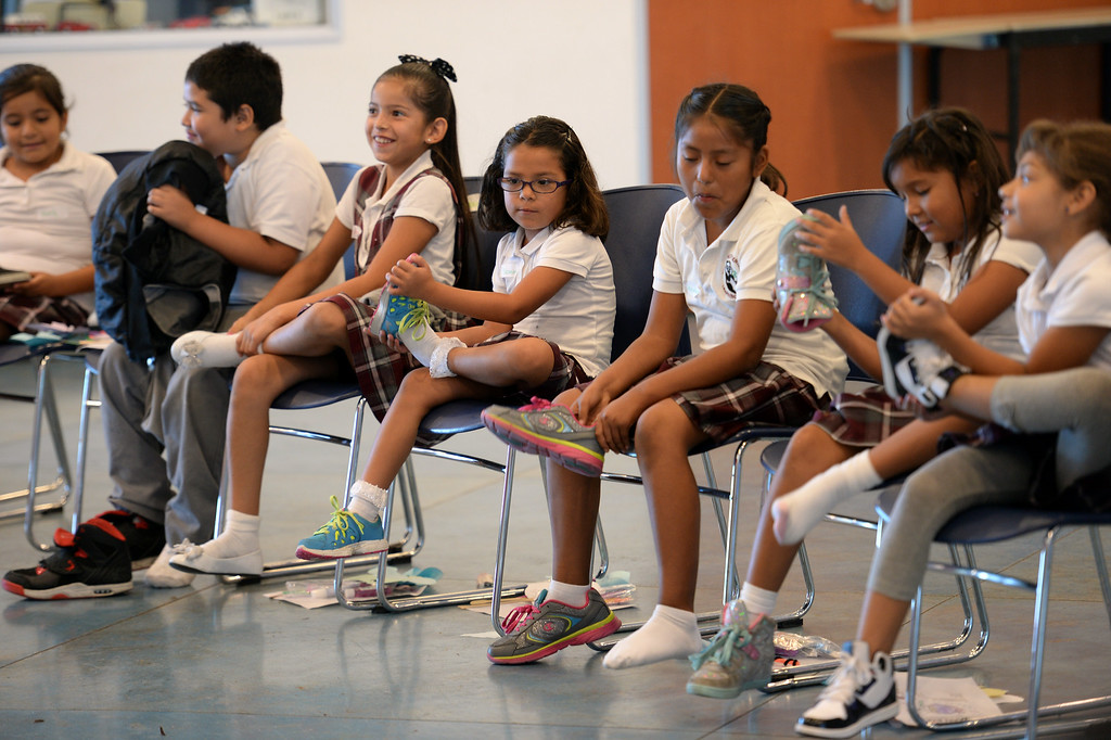 . Children try on shoes during MEND�s (Meet Each Need with Dignity) 13th annual �Head to Toes,� program at the Pacoima charity�s center Wednesday, August 27, 2014. 240 third-graders from Pacoima�s Vaughn Next Century Learning Center were provided with full back-to-school care: free dental and vision screenings through a healthcare initiative with Verizon Foundation, new shoes and new backpacks chock-full of school supplies school supplies donated by the Ella Fitzgerald Charitable Foundation. (Photo by Hans Gutknecht/Los Angeles Daily News)