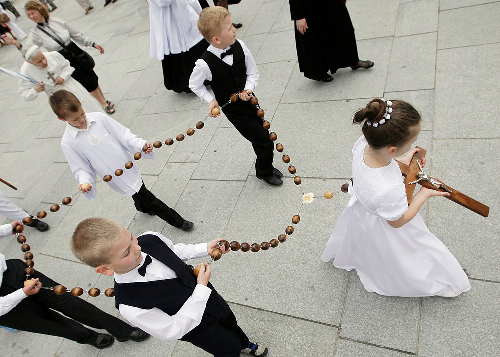 . Children carry a giant rosary during a Corpus Christi procession in Warsaw, Poland, Thursday, May 30, 2013. Corpus Christi is a national holiday centering on processions in this predominantly Roman Catholic nation. (AP Photo/Czarek Sokolowski)