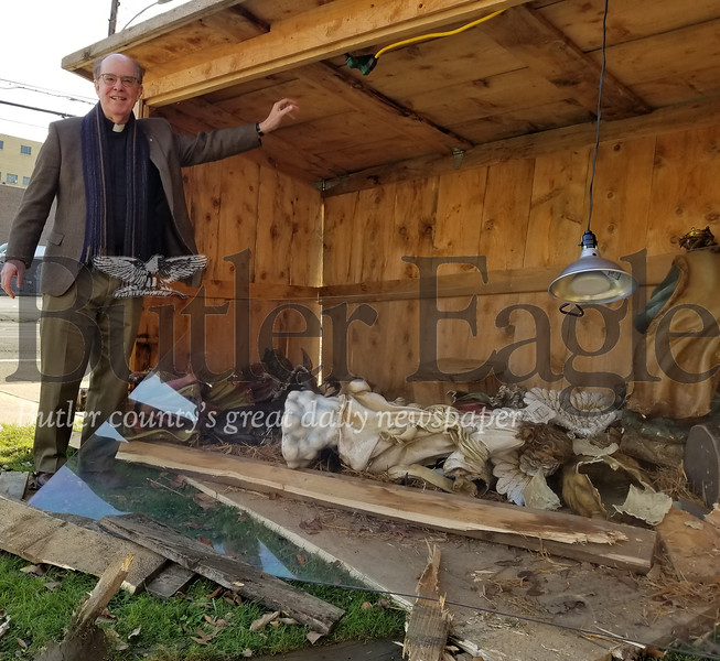 The Rev. Al Towberman, senior pastor of the St. Mark's Lutheran Church, examines the damage done to the church's nativity scene after a vehicle accident crushed the manger Wednesday night. Photo by Nathan Bottiger.