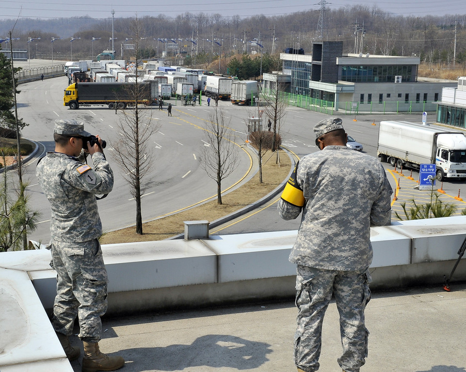 """. US soldiers take pictures as South Korean trucks return back after they were banned access to Kaesong joint industrial park in North Korea, at a military check point of the inter-Korean transit office in Paju on April 3, 2013. North Korea blocked South Korean access to a key joint industrial zone on April 3, in a sharp escalation of tensions as Washington condemned Pyongyang\'s \""""dangerous, reckless\"""" behaviour. AFP PHOTO / JUNG YEON-JE        (Photo credit should read JUNG YEON-JE/AFP/Getty Images)"""