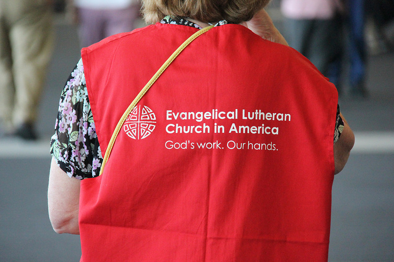 Many volunteers are identified by their red vests.