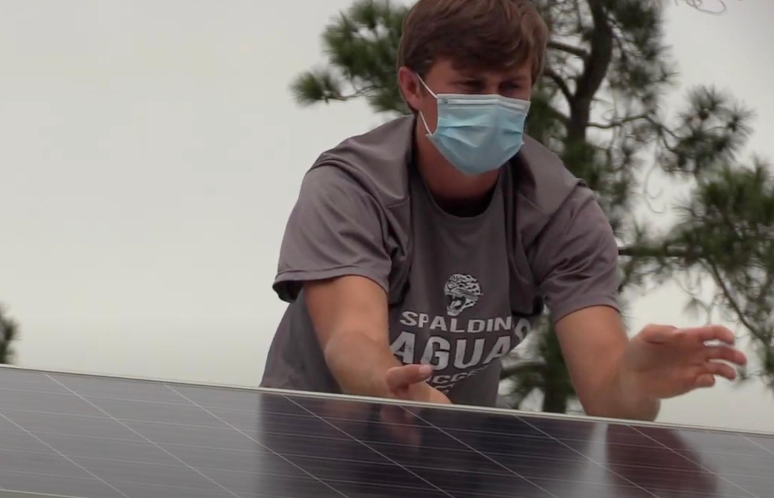 Alumnus Bo Cavender installs solar panel at BCHS.