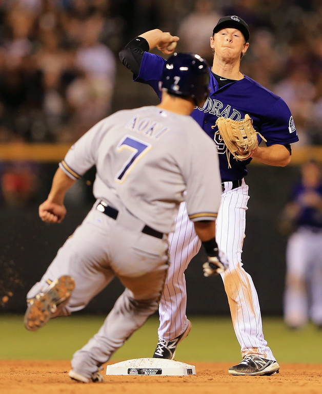 . DENVER, CO - JULY 26:  Second baseman DJ LeMahieu #9 of the Colorado Rockies turns a double play on Norichika Aoki #7 of the Milwaukee Brewers on a ball hit by Jean Segura #9 of the Milwaukee Brewers to end the eighth inning at Coors Field on July 26, 2013 in Denver, Colorado.  (Photo by Doug Pensinger/Getty Images)