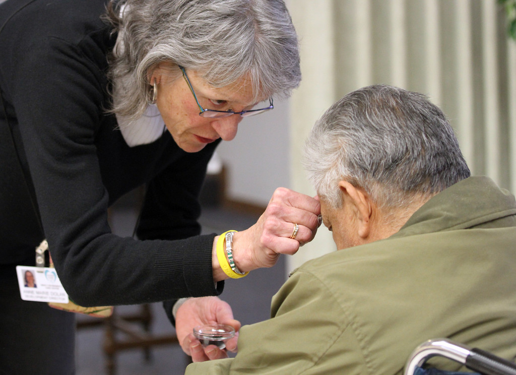 . Development Director Anne Dolan applies ash to the forehead of one of many seniors in attendance at the Ash Wednesday Mass at the Mercy Retirement & Care Center in Oakland, Calif. on Wednesday, Feb. 13, 2013.  Father Larry Dunphey, O.F.M., a Franciscan Priest,  comes to the Senior Care Center to deliver Mass for the many seniors who are unable to travel outside of the center.  Mass is delivered every Sunday at the center where the average age is 91 years old and 90% of the residents are catholic.  During Lent, they will have Stations of the Cross prayer service every Friday at 2:00 pm. (Laura A. Oda/Staff)