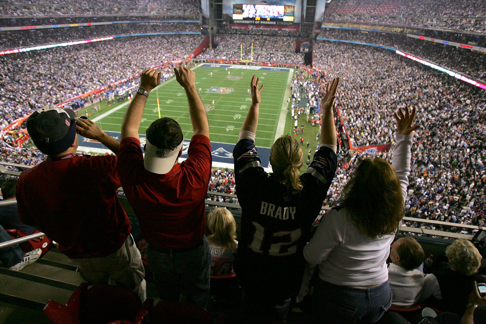 Description of . Fans cheer on the New England Patriots against the New York Giants during Super Bowl XLII on February 3, 2008 at the University of Phoenix Stadium in Glendale, Arizona. The Giants defeated the Patriots 17-14. (Photo by Doug Pensinger/Getty Images)