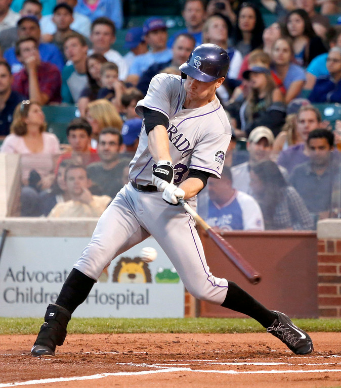 . Colorado Rockies\' Justin Morneau hits a two-run double off Chicago Cubs starting pitcher Edwin Jackson, scoring Nolan Arenado and Carlos Gonzalez, during the first inning of a baseball game Tuesday, July 29, 2014, in Chicago. (AP Photo/Charles Rex Arbogast)