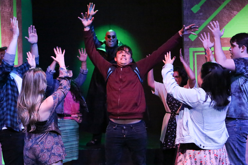 The cast of BE MORE CHILL singing the title song, with Jeremy (Jayde Mitchell) center, and The Squip (Dominic Dowdy-Windsor) in back, New Line Theatre, 2019. Photo credit: Jill Ritter Lindberg.