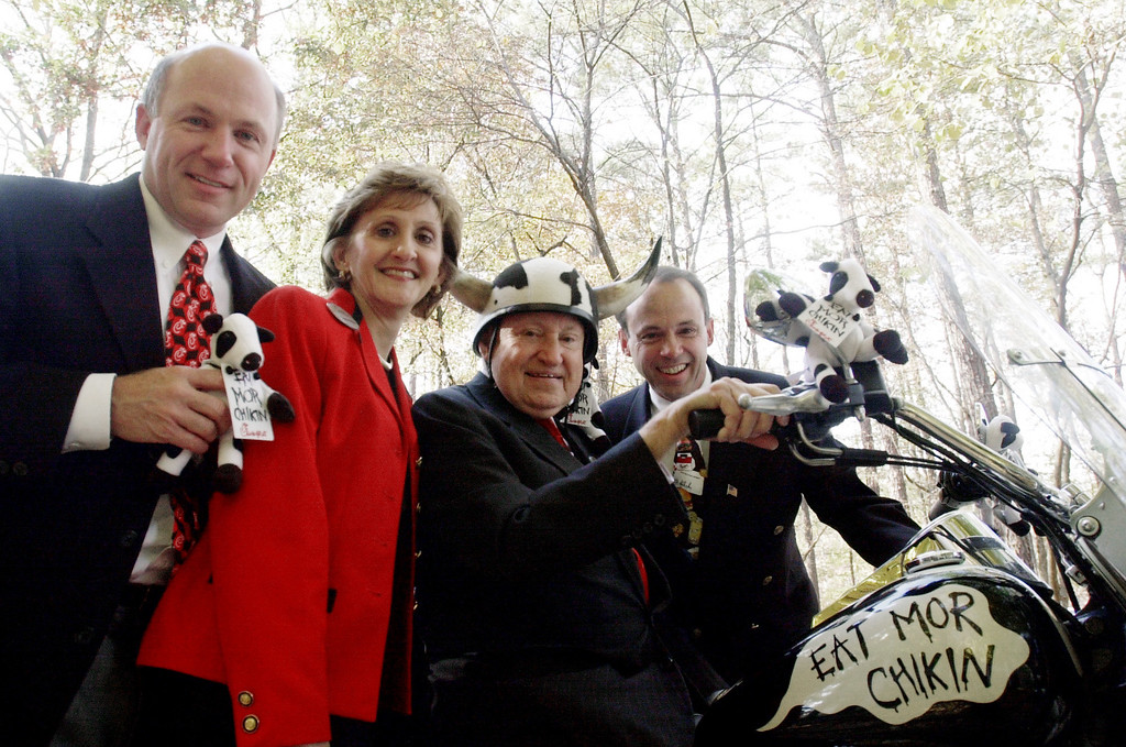 ". S. Truett Cathy, founder of Chick-fil-A, second right, poses Thursday, Nov. 8, 2001, on his son, Dan T. Cathy\'s, Harley Davidson motorcycle painted to look like a cow, at the company\'s headquarters in south Atlanta. Joining Cathy are, from left, son Dan T. Cathy, daughter Trudy White, and son Donald ""Bubba\"" Cathy. (AP Photo/Ric Feld)"