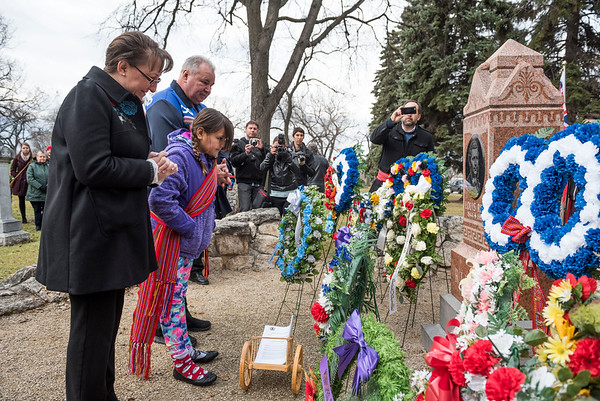 President of the Manitoba Metis Federation David Chartrand along with his wife Glorian and granddaughter Martha lay a copy of the historical framework agreement with the Government of Canada at Louis Riel's grave Wednesday November 16, 2016 during the Louis Riel Commemoration Ceremony at the St. Boniface Basilica Grounds. (David Lipnowski for Metro News)