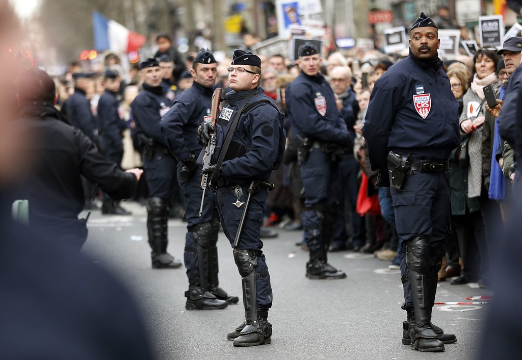 . French riot police keep watch during a Unity rally Marche Republicaine in Paris on January 11, 2015 held in tribute to the 17 victims of the three-day killing spree. The killings began on January 7 with an assault on the Charlie Hebdo satirical magazine in Paris that saw two brothers massacre 12 people including some of the country\'s best-known cartoonists and the storming of a Kosher supermarket on the eastern fringes of the capital which killed 4 local residents. eson January 7 with an assault on the Charlie Hebdo satirical magazine in Paris that saw two brothers massacre 12 people including some of the country\'s best-known cartoonists and the storming of a Kosher supermarket on the eastern fringes of the capital which killed 4 local residents.   AFP PHOTO / THOMAS SAMSONTHOMAS SAMSON/AFP/Getty Images