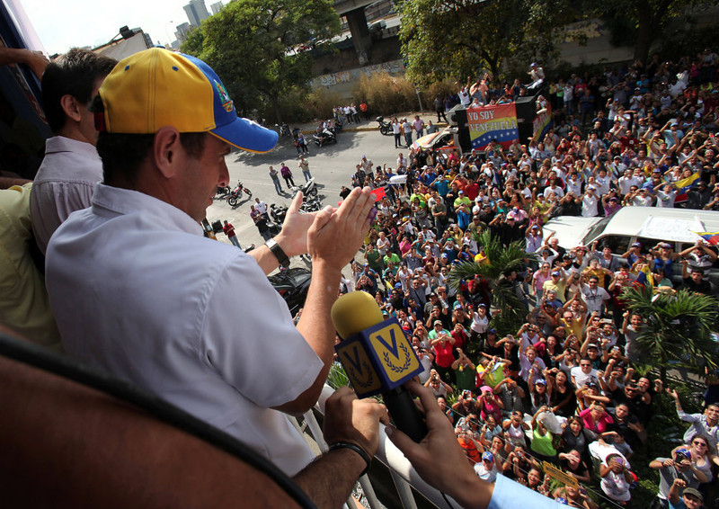 . Opposition presidential candidate Henrique Capriles greets supporters from the window of his campaign headquarters in Caracas, Venezuela, Monday, April 15, 2013. Venezuela\'s government-friendly electoral council indicated Monday it would quickly certify the presidential victory of Hugo Chavez\' hand-picked successor Nicolas Maduro, apparently ignoring opposition demands for a recount in Sunday\'s tight race. (AP Photo/Fernando Llano)